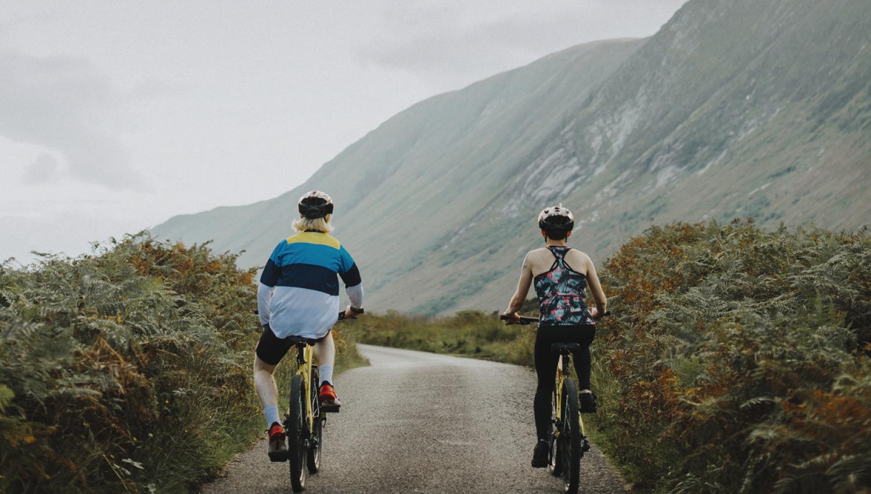 couple biking down a road in scotlands hillside